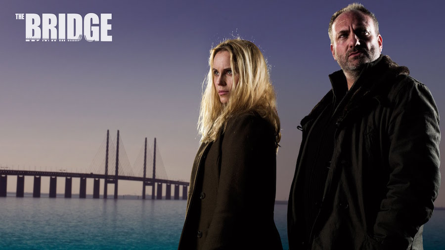"DVD Review– The Bridge (bron ||| broen): Season 3 and The Tunnel: Sabotage (Season 2) Since it first aired in 2011, The Bridge has become an international phenomenon. Originally (bron ||| broen) a Danish/Swedish co-production, it opened with an intriguing premise: a dead body is found directly in the center of a bridge connecting Denmark and Sweden. Upon further investigation, the corpse consists of parts of two different bodies, each cut in half. Two very different detectives, one Danish, one Swedish, band together to investigate, but the initial mystery deepens as a serial killer with a bizarre agenda starts striking again and again. The show was a critical and popular hit, and soon an American version set between the United States and Mexico followed, then another version between the U.K. and France appeared, and a Russian/Estonian version (as yet unseen by me) entered the franchise, too. The American/Mexican version was cancelled too soon, after just two seasons, but the other series are still in progress. Recently, the third season of the Danish/Swedish original was released on DVD, with a fourth and final season in production. Comparably, the second season of the U.K./French version (The Tunnel, so named because the initial crime takes place in the Chunnel) just came out on DVD, with a third and final season planned. The first seasons of the American/Mexican and U.K./French versions followed the Danish/Swedish series fairly closely, though the second seasons of both went in radically different directions. Though the Danish/Swedish, American/Mexican, and U.K./French versions all started at roughly the same point, they all diverged thematically and in terms of character development as well. The Danish/Swedish and American/Mexican versions have achieved excellence, albeit in strikingly different ways. Unfortunately, the U.K./French version, though blessed with a talented cast, ultimately can't manage to do justice to the material. The heart and soul of the Danish/Swedish version has always been Sofia Helin as Saga Norén, a Swedish police officer who's brilliant at her job but who is socially awkward, due to undiagnosed Asperger's Syndrome. Saga finds it hard to understand why other people behave as they do, though she gradually strengthens her social skills over the course of the series. Helin's inspired performance is a joy to watch, and in the third season of The Bridge, where a serial killer starts targeting victims such as the lesbian founder of a gender-neutral preschool, at first Saga's character covers ground we've already seen before. As the series progresses, however, Helin begins to turn in her finest work yet as Saga is dragged into darker, bleaker, and lonelier emotional depths than she's ever faced before, wrestling with the fallout of her own dysfunctional family. The first two seasons of the Danish/Swedish The Bridge are absolutely required viewing before seeing the third. Plotwise, the second and third seasons are solid, though nothing quite matches the heights of season one. Character-wise and tonally, the third season still packs a massive punch, as an investigation that initially seems to be based around social issues turns out to be predicated in the after-effects of a broken heart. The U.S./Mexican adaptation is a great example of how to make an Americanization of another country's series work. It provided its own great cast, enhanced the character development of some supporting characters, and skillfully transplanted the setting, adding commentary on American/Mexican relations that never became preachy, and which actually cleverly critiqued and subverted many frequent talking points on politics, crime, and international relations. The U.K./French The Tunnel, in contrast, takes quality material and squanders the potential. The first season was pretty decent, thanks to its superb cast, but the second season devolves into a disappointing thematic and moral mess. While Saga (and Diane Kruger's Sonya in the U.S. version) were always the soul of their respective series, in The Tunnel, Stephen Dillane as Karl Roebuck, the male half of the investigating team, makes by far the bigger impact, due to his understated charisma and some poor writing decisions in developing his female co-lead. Dillane's an absolute delight in the role. Absolutely no fault whatsoever should be ascribed to Clémence Poésy, who's very good as Elise Wassermann, but in the special features to the first season, the creative team said that they were trying to move away from ascribing Elise's personality quirks to the autism spectrum. This is a fatal mistake. The Aspergerian Saga and Sonya's social clumsiness, frequent faux pas, and constant confusion at their co-workers' perceived shortcomings, are inherent to their characters. Meanwhile, if the writers aren't giving Elise a form of autism, they're stressing her reserved and brusque demeanor as emotional repression. When Saga is a guest to dinner at someone's home and says that the food isn't tasty, that's because she never dreams that her comment might hurt her hostess's feelings. When Elise says the food is bland and needs Tabasco, it's just rude. Not only that, but Elise is blander than her sister characters in other ways. For example, Elise's wardrobe is less striking than Saga's and Sonya's, who used leather clothing to distinguish themselves as different and distinctive characters. Saga wears the same flowing coat, sweater, and leather pants every day, and Sonya's distinctive leather jacket, covered in artwork and idiosyncrasies—and which was only revealed to the viewer a little at a time—was a character in itself. But Elise looks more or less like everybody else. Saga and Sonya can learn how to connect with other people better, but their unique and wonderful minds will never be neurotypical. In contrast, Elise seems to be set up as an ice queen, and while the character arcs of Saga and Sonya can have them understand humanity better while remaining wholly themselves, the emotional arc of an ice queen is usually to melt, and it's the second season and its treatment of Elise's romantic relationship that leave a sour taste to the whole proceedings. Without too many spoilers (though by necessity some follow), Season Two of The Tunnel starts with a mysterious plane crash that may be terrorism. This makes for a great scene for Dillane, as he gives a powerful performance mourning the loss of innocent lives. Late in the series, one character turns out to be complicit in the crime, and arrogantly and self-righteously announces that the ""less hypocritical"" side was chosen. Yet The Tunnel wants to make Elise's relationship with this person a beautiful thing when, in fact, the character in question is a cold-blooded killer, and even though there's a quick and partial act of redemption, it's not nearly enough by a long shot. What's worse is that Roebuck dismisses Elise's uncertainty as being ""in love,"" when the person in question is actually a cold-blooded killer. All his righteous indignation from several episodes earlier evaporates in a puff of misguided sentimentality. It's a horribly handled series of scenes, which undercuts the tragedy of numerous innocent lives lost, and it cheapens and tarnishes the characters of both Elise and Karl. The Danish/Swedish and American/French versions of The Bridge succeed in part because the heroine always keeps her moral compass. There's a powerful scene at the end of the third season where Saga wavers, but eventually makes the right decision. However, the realization that she came close to not doing the right thing shakes her, and it gives The Bridge a weight and depth that a show with a broken conscience like The Tunnel cannot hope to achieve. The Tunnel has always been marred by its clumsy politics as well. Both versions of The Bridge address political issues, but the Danish/Swedish series skillfully avoids preachiness and always shows that violence in the name of activism is wrong. In contrast, The Tunnel, through the comments of some characters and some clumsy diatribes and ham-fisted sequences, editorializes at the expense of narrative, and at times seems to romanticize—or at least show a slightly hidden respect—for those who use bloodshed to point out social ills. Visually, The Tunnel lacks the punch of its peers, too. The Tunnel looks like a hundred other British shows, but the Danish/Swedish The Bridge's cinematography is notable for its clear, cold starkness, and the American/Mexican The Bridge makes the hot desert environment a palpable force. The Tunnel had a lot of potential, but without cleverer and more ethically perceptive writers, it remains a disappointment and a waste of fine actors. Comparatively, both the Danish/Swedish and the American/Mexican versions of The Bridge are outstanding television because they never lose track of their heads, hearts, and characters. –Chris Chan The Bridge (bron 